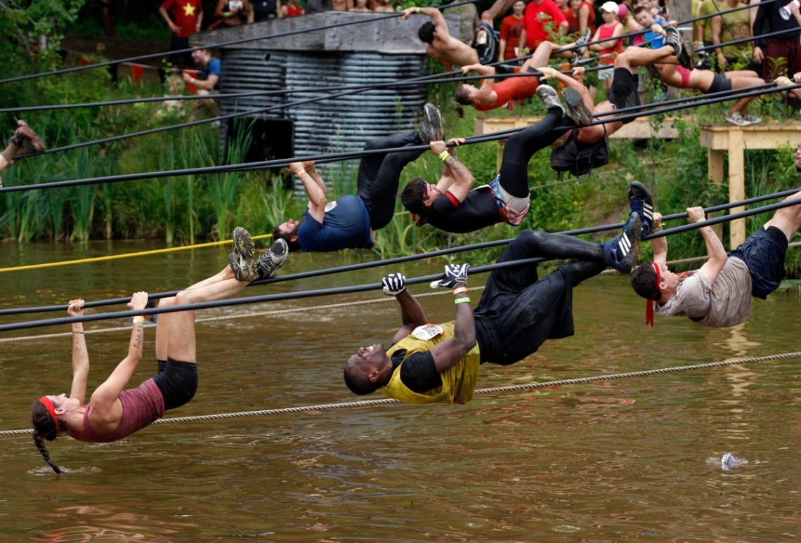Competitors pull themselves over water along a rope during the Tough Mudder at Mt. Snow in West Dover